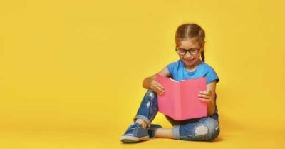 girl with glasses reading happily