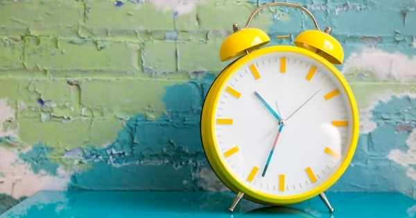 yellow clock teal brick wall